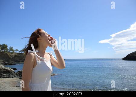 Une femme heureuse en robe blanche criant sur la plage vacances d'été
