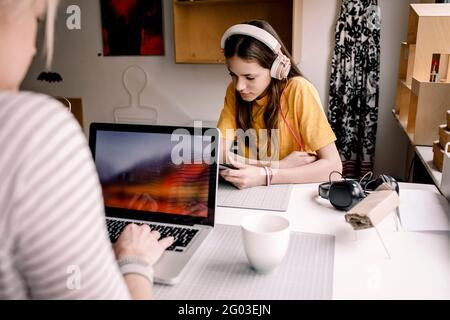 Fille portant un casque E-learning via une tablette numérique tout en étant assise avec une femme d'affaires travaillant sur un ordinateur portable au bureau