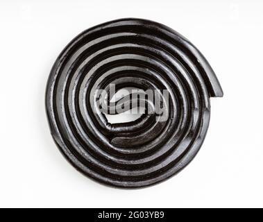vue de dessus de la spirale de bonbons de réglisse noir sur blanc plaque