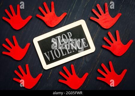 Panneau stop violence et mains rouges sur la surface sombre.