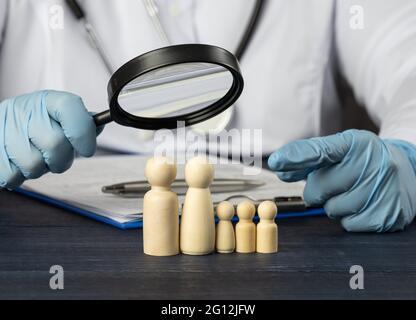 le médecin de famille tient une loupe sur une figurine en bois. Concept de recherche médicale, méthodes de traitement. La nécessité d'une assurance médicale.
