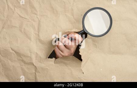 la main d'une femme tient une loupe en verre, une partie du corps dépasse d'un trou en papier brun. Concept de recherche de solution, recherche.
