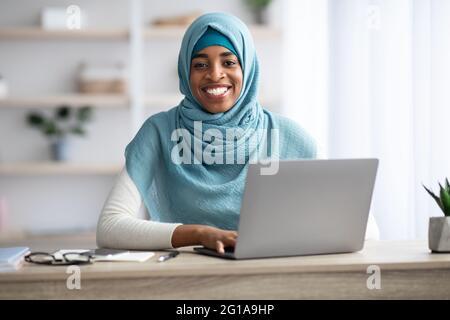 Freelance. Femme musulmane africaine en hijab travaillant avec un ordinateur portable au bureau à domicile