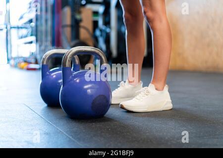 Courte inreconnaissable athlète féminine déterminée dans des vêtements de sport debout après se reposer pendant l'entraînement fonctionnel avec des poids sur le sol dans la salle de sport