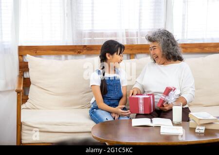 Grand-mère asiatique et petite-fille ouvrent la boîte cadeau rouge dans le salon à la maison pendant le festival du nouvel an ou la fête d'anniversaire. Moment de bonheur et fami