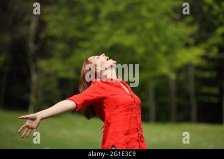 Femme excitée en rouge criant à l'air étirant les bras dans une forêt