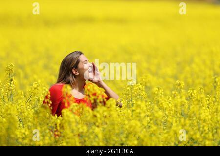 Portrait d'une femme heureuse en rouge criant dans un champ jaune au printemps