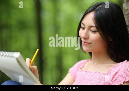 Femme heureuse asiatique tirant sur un ordinateur portable assis dans un parc
