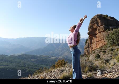 Portrait de vue latérale d'une femme excitée célébrant des vacances levant les bras dans la montagne