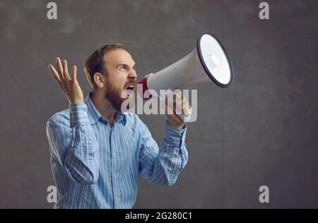 Un jeune homme d'affaires excité dans une chemise bleue tenant un mégaphone et criant comme fou