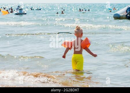 Antalya, Turquie-septembre 11, 2017: Joli petit garçon avec des brassards gonflables se préparer à nager dans la mer dans une chaude journée d'été à Antalya, Turquie.