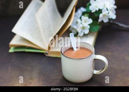 Une ambiance feutrée de Pâques et de printemps. Une tasse de café, un livre, une branche florissante d'un pommier sur un fond sombre. Photo de style vintage pour femme,