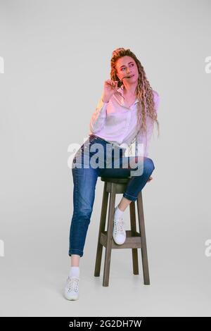 Une femme heureuse en Jean et une chemise en coton avec des dreadlocks est assise sur une chaise sous des lumières colorées