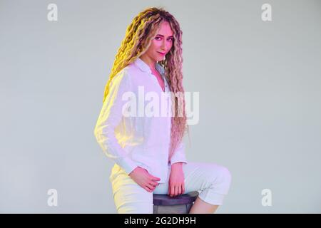Femme délicate dans un chemisier blanc et un pantalon sous une lumière fluo