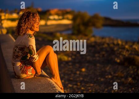 Une femme s'assoit à l'extérieur et profiter de la lumière du coucher de soleil regardant devant elle - plage et océan en arrière-plan - tourisme et vacances d'été Voyage style de vie personnes concept