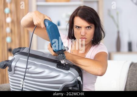 femme caucasienne en colère essayant d'ouvrir une valise avec un perceuse électrique