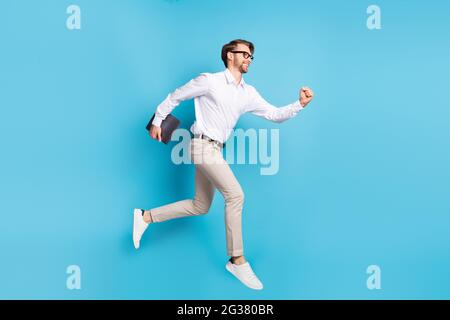 Vue sur toute la longueur de la taille du corps attrayant homme gai sautant courir portant un ordinateur portable isolé sur fond bleu vif
