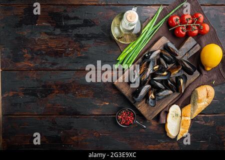 Moules cuites à la vapeur dans un décor de vin blanc, sur une planche à découper en bois, sur un arrière-plan de table en bois foncé, sur un plan de dessus, avec copyspace et espace pour le texte