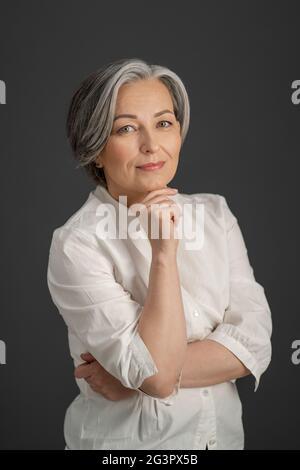 Belle femme aux cheveux gris sourit doucement tout en touchant son menton avec la main et en regardant l'appareil photo. Intelligente belle maturité