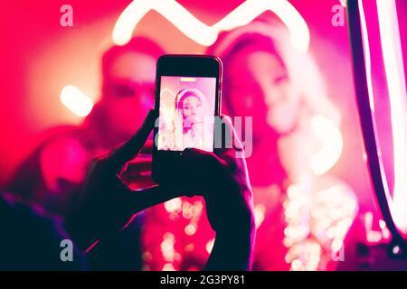 Une jeune femme est photographiée dans une boîte de nuit. Concentrez-vous sur les mains de sexe masculin pour prendre des photos avec un smartphone au premier plan. Abstrait flou de dos