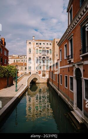 Un canal étroit à Venise. Petits canaux entre maisons, à quelques mètres. De beaux petits ponts entre les rues.