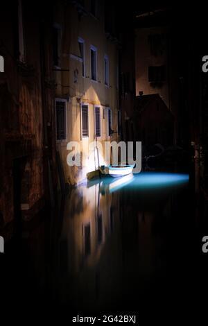 Vue sur un bateau éclairé et pêcher dans un canal à San Marco la nuit, Venise, Vénétie, Italie, Europe