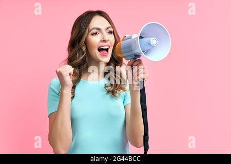 Jolie jeune femme criant au mégaphone sur fond rose