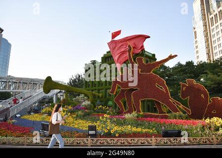 Pékin, Chine. 19 juin 2021. Une femme passe devant des décorations florales établies le long de l'avenue Chang'an à Beijing, capitale de la Chine, le 19 juin 2021. Credit: Chen Zhonghao/Xinhua/Alay Live News