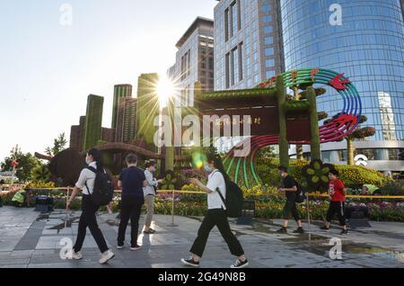 Pékin, Chine. 19 juin 2021. Les gens marchent devant des décorations florales établies le long de l'avenue Chang'an à Beijing, capitale de la Chine, le 19 juin 2021. Credit: Chen Zhonghao/Xinhua/Alay Live News