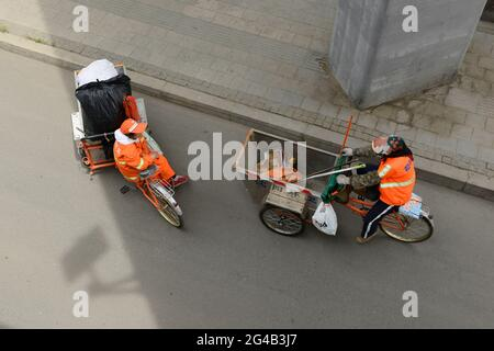 Les balayeurs de rue sur les tricycles caoutchoutés font une pause et ont une discussion au bord de la route à Shenyang, en Chine