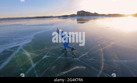 La jeune fille s'entraîne sur le patinage de vitesse sur glace. L'enfant skate en hiver dans un costume bleu de sport, des lunettes de sport. Sports de patinage de vitesse pour enfants.