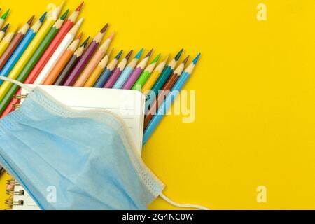 Retour à l'école, concept du coronavirus pandémique, composition de la pose à plat, fournitures scolaires et papeterie sur le bureau jaune, espace de copie et vue du dessus