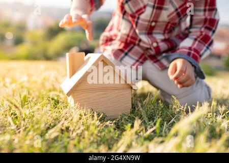 Garçon jouant avec un jouet de maison en bois sur l'herbe pendant la journée ensoleillée
