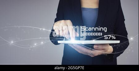 Concept de numérisation futuriste et technologique. Tablette blanche en main femme d'affaires avec signature numérique hologramme sur fond gris