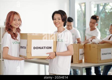 Des amies souriantes portant une grande boîte de vêtements donnés, leurs collègues trient des articles en arrière-plan