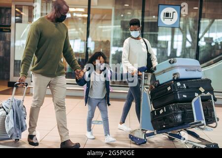 Homme et femme avec une jeune fille voyageant pendant une pandémie à l'aéroport. Famille africaine de trois personnes marchant au terminal de l'aéroport portant des masques.