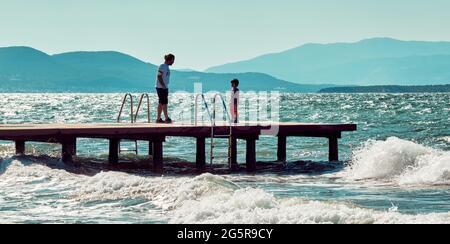 Urla, İzmir, Turquie - juin 2021 : un père parle à son fils sur un ponton en bois au-dessus de la mer à Urla, İzmir, Turquie.