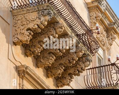 Noto, Syracuse, Sicile, Italie. Des figures de pierre finement sculptées soutenant un balcon ornemental sur la façade baroque du Palazzo Nicolaci di Villadorata.