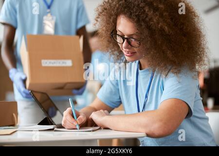 Une jeune femme volontaire prend des notes et un gars portant une boîte en carton à l'arrière-plan tout en travaillant sur le projet de don à l'intérieur