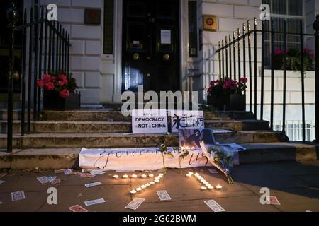 Les manifestants laissent des fleurs et des bougies allumées devant le Bureau économique et commercial de Hong Kong pour pleurer la mort d'un Hongkonger pendant la manifestation. Les Hongkongais ont organisé des manifestations dans dix villes différentes du Royaume-Uni pour protester contre le premier anniversaire de la promulgation de la loi sur la sécurité nationale de Hong Kong et le centenaire du Parti communiste chinois. À Londres, les participants se sont rassemblés devant l'ambassade de Chine et ont défilé dans le quartier chinois où l'événement principal a eu lieu. Les foules se sont ensuite déplacées vers le bureau économique et commercial de Hong Kong et ont mis des torches fumances à l'extérieur