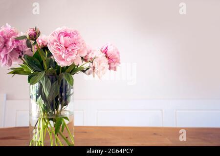 Un bouquet de pivoine rose pastel avec des feuilles vertes dans un vase en verre sur la table en bois près de la texture de mur blanc, décoration lumineuse et confortable pour une maison élégante