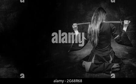 portrait complet d'une jeune femme à cheveux longs portant un costume médiéval. pose assis avec une épée sur ses épaules, sur fond sombre de studio avec