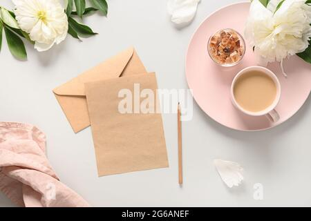 Petit déjeuner romantique d'été avec tasse de café et fleurs de péonies blanches sur le bureau gris. Vue du dessus, plan d'appartement. Lettrage concept Elegance. Greeti