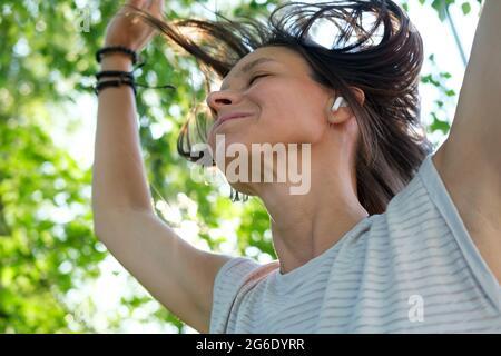 Une femme heureuse écoute de la musique dans des écouteurs sans fil et danse, avec ses cheveux en vol, un jour ensoleillé d'été.