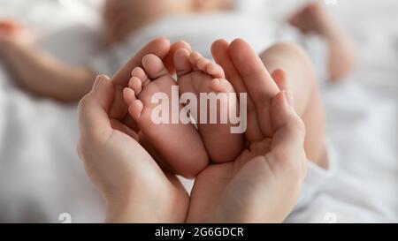 Gros plan des petits pieds de nouveau-né dans les mains de la mère