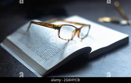 Une paire de lunettes de lecture reposant sur un livre ouvert.