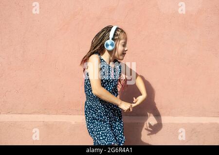Une petite fille adorable qui écoute de la musique et danse avec un casque.