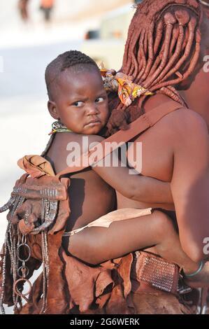 NAMIBIE. FEMME HIMBA PORTANT SON ENFANT SUR LE DOS. POUR LE PEUPLE HIMBAS, LES FEMMES ONT BEAUCOUP DE POUVOIRS COMME LA PROPRIÉTÉ DE CERTAINS DE LA VIE STOC