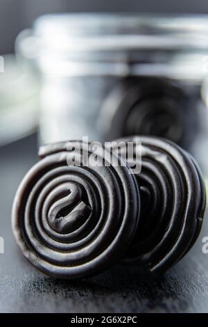 Spirale de bonbons de réglisse sur table noire.