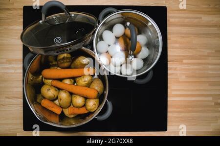 faire bouillir les œufs et les légumes dans des casseroles sur une plaque de cuisson à induction céramique